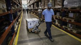 warehouse worker moving Pfizer COVID-19 vaccine